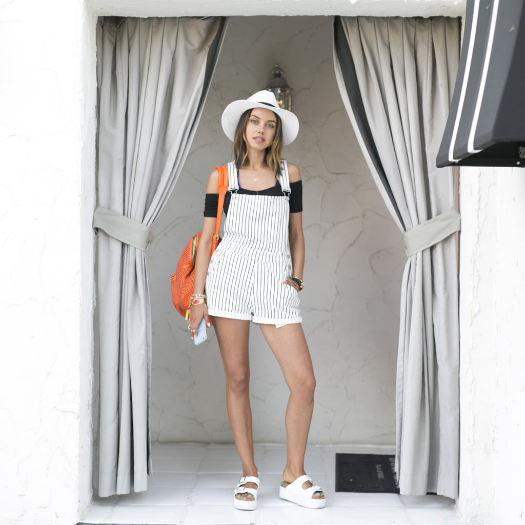 Pin-striped overalls were made chic with a black off-the-shoulder crop top, platform sliders, and a fedora.