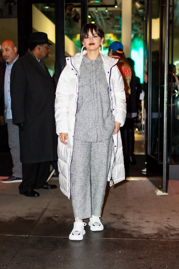 "Selena Gomez can perform a style switch-up at the drop of a hat. Just a day after appearing on The Tonight Show in a retro Miu Miu dress, the ""Look At Her Now"" singer stepped out in NYC wearing its polar opposite: a houndstooth Totême set with a white full-length puffer coat from Everlane. Is anyone else getting major Billie Eilish vibes from this outfit? Selena showed off the ensemble for a meet and greet to promote her newly-released album at a Puma pop-up shop, and she looked fierce.  Selena paired the bold matching set with Puma sneakers and oversized Fenty hoop earrings. Oh, did I forget to mention her stylist Kate Young threw a Cartier chain on their too? It's rumored to be above $7,000. That must definitely make Selena feel rare! Ahead, see more photos of Selena's look from her night out in NYC."