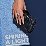She met a snakeskin clutch with a royal-blue wraparound snake ring.