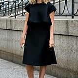 When you have a highly structured black dress, streamlining the rest of the look — black-and-white heels and tortoiseshell cat-eye sunglasses — keeps the attention where you want it.