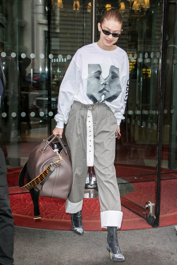 Wearing an oversize Chaos sweatshirt with Stuart Weitzman booties and a Fendi duffel bag.