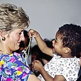 Diana let a little girl play with her necklace while visiting a hostel for abandoned children suffering from AIDS in São Paulo, Brazil, in April 1991.