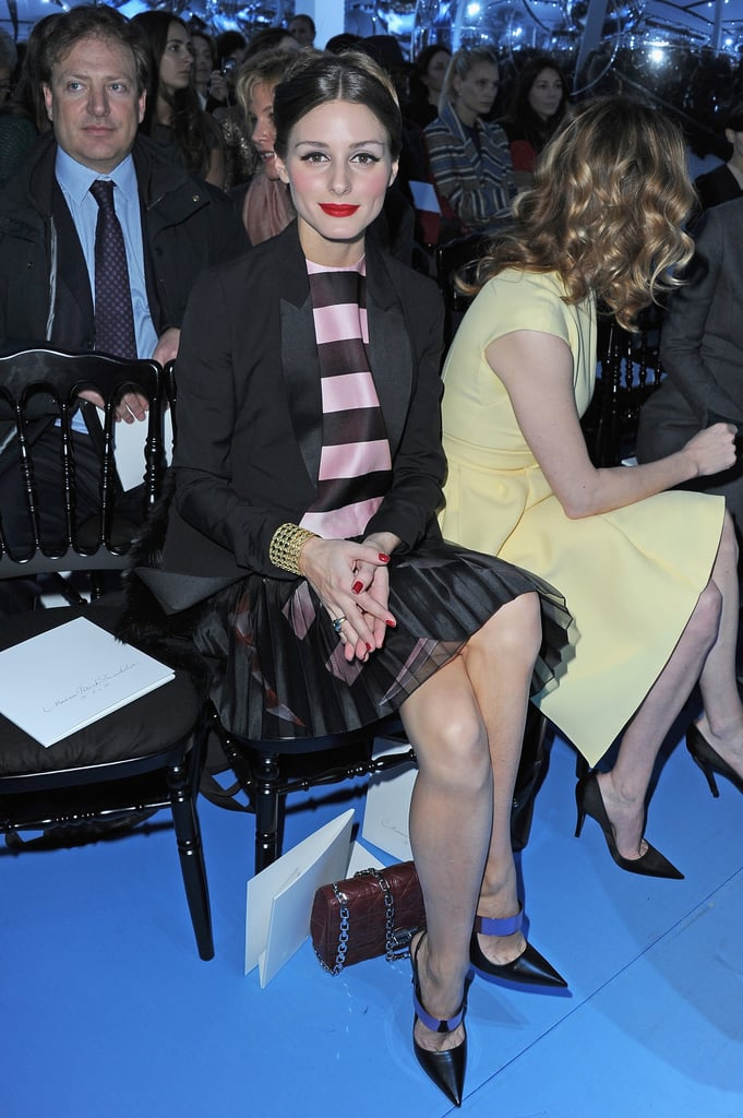 Olivia Palermo worked a flirty semi-sheer, striped dress sitting front row at Christian Dior. Mirrored-strap pumps, a quilted Dior bag, and red lipstick completed her flawless look.