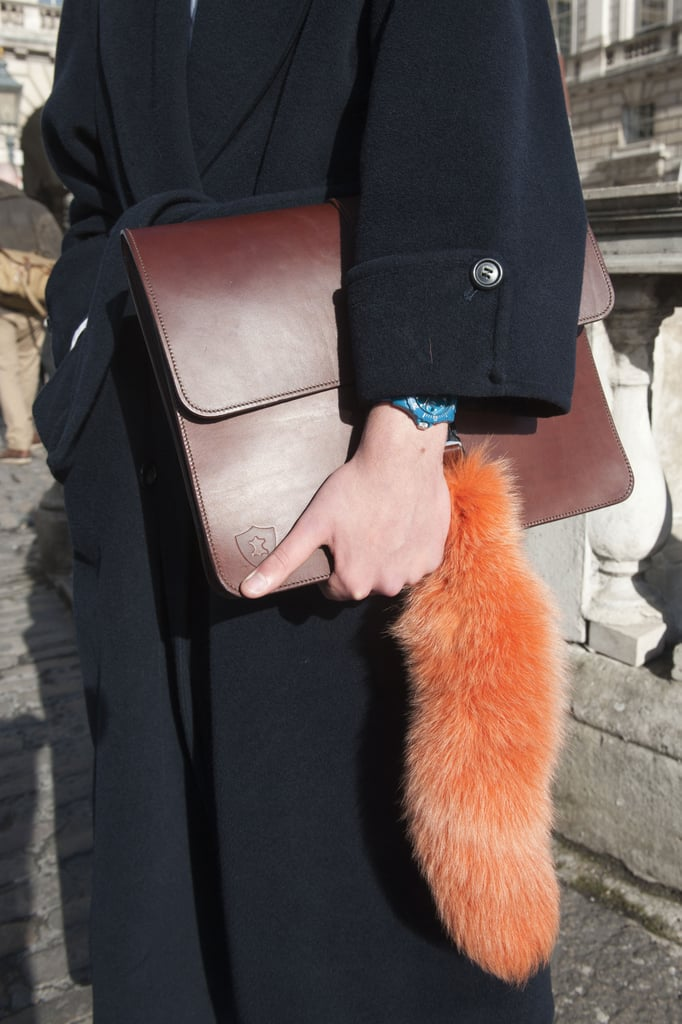 A classic brown portfolio clutch got updated with a furry orange detail.