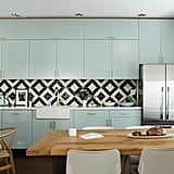 The kitchen is pure perfection: pastel mint green cabinets are dressed up with brass hardware and placed against a gorgeous black and white diamond print backsplash (DIYers, you could hand paint something similar!). Light wood furniture ties everything together.