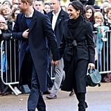 In January 2018, Meghan ditched the royal protocol by wearing a jet-black outfit, which she accessorized with a green DeMellier handbag.