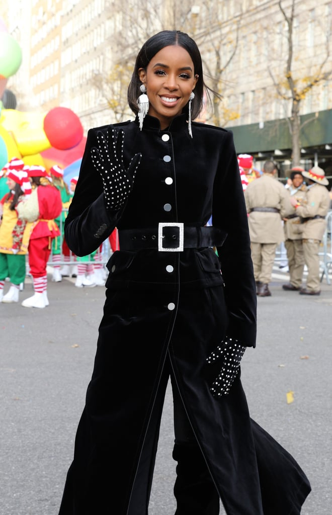 Kelly Rowland gave us a lesson in how to stay stylish while staying warm when she put in an appearance at the Macy's Thanksgiving Day Parade on Thursday. The former Destiny's Child singer — who's starring in a Christmas movie this year — wrapped up in a luxurious ankle-length velvet coat with military-inspired buttons and a stand-up collar, and proved that sometimes, outerwear can be an outfit in itself. What she's wearing underneath really didn't matter with all eyes on that statement coat. To contrast the sharp lines of the coat, Kelly piled on some festive sparkle by opting for bejeweled silver accessories, namely a diamanté belt, leather gloves studded with crystals, and giant chandelier earrings. She took great pride in showing off her gloves as she posed for the cameras, and who can blame her: if you're going to wrap up warm, you may as well do so with a touch of sparkle. Keep reading for a closer look at the whole dazzling outfit.