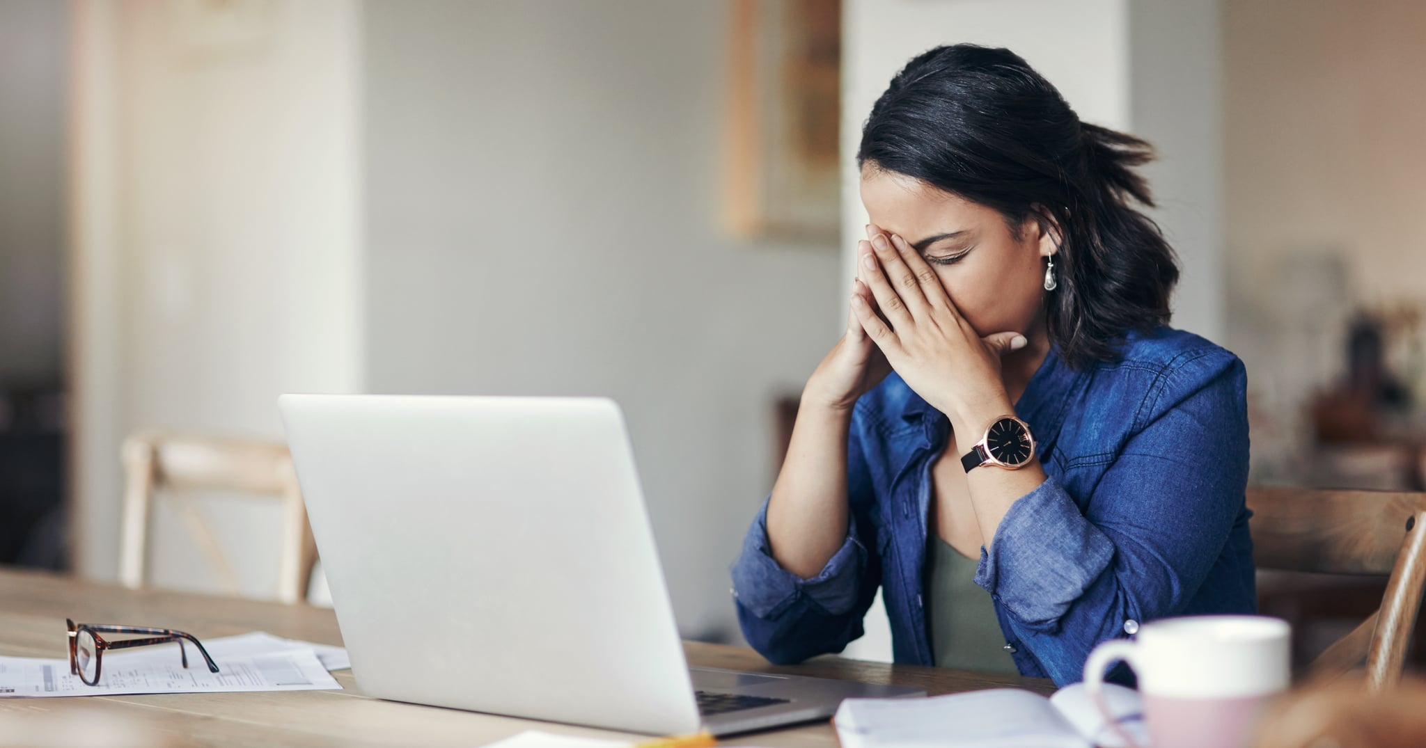 Shot of a young woman looking stressed while using a laptop to work from home