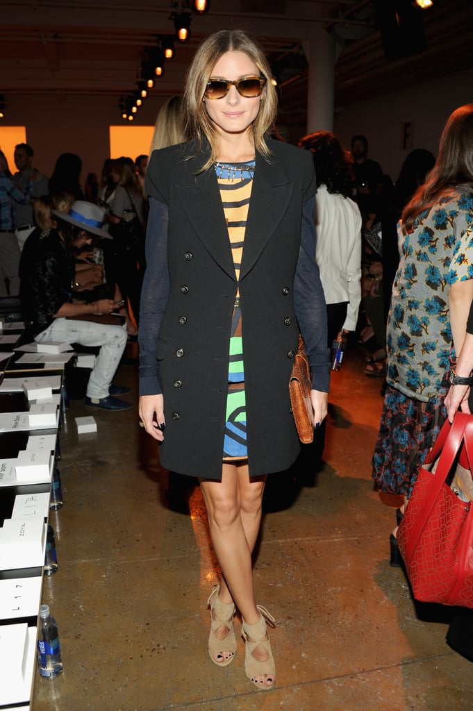 Olivia Palermo layered a black vest over a colorful minidress, then injected major cool via Ray-Ban sunglasses, a tan clutch, and taupe cutout booties at Peter Som.