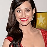 Emmy Rossum went for full-on glamour with bright red lips, glossy waves, and a subtle liner look.