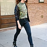 Lily Aldridge making a camo-print tee, baseball jacket, and skinny jeans look glam with edgy heels.
