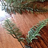 He clipped plastic ferns apart to make sprigs for the branches.