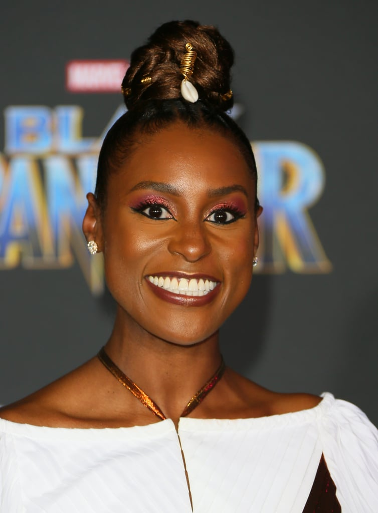 Issa Rae is living her best life right now, and it shows all over her face — that glow is real! The 33-year-old attended the premiere of the highly anticipated Black Panther in her royal best. She wore a multicolored dress, which complimented her makeup look perfectly. For her base, the CoverGirl wore the Vitalist Healthy Elixir Foundation ($6) in soft sable and Vitalist Highlighter ($11) in Daybreak to achieve that glow. For her eyes, Issa rocked a stunning cranberry eye shadow with subtle glitter, pairing it with the CoverGirl Get in Line Eyeliner in Major Matte Black ($8) and the Peacock Flare Mascara ($9). Her makeup artist, Joanna Simkin, brought it all the way down past the corner of her eye to give it that Cleopatra touch and finished it off with the Melting Pout Matte in All Nighter ($7). If you do the math, it's comes out to $41 to achieve this gorgeous makeup look. The best part? You can create so many other looks, so you really get your money's worth. Keep scrolling to bask in Issa and all her goddess glory.