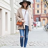 With a White Sweater, a Cream-Colored Coat, and Distressed Denim
