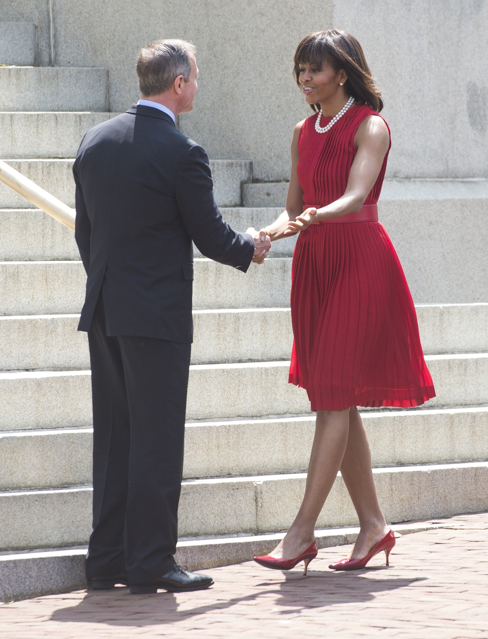 Michelle Obama chose a red pleated Michael Kors dress — complete with matching low-heeled pumps and a double strand of pearls — for a bill signing in Maryland in April.