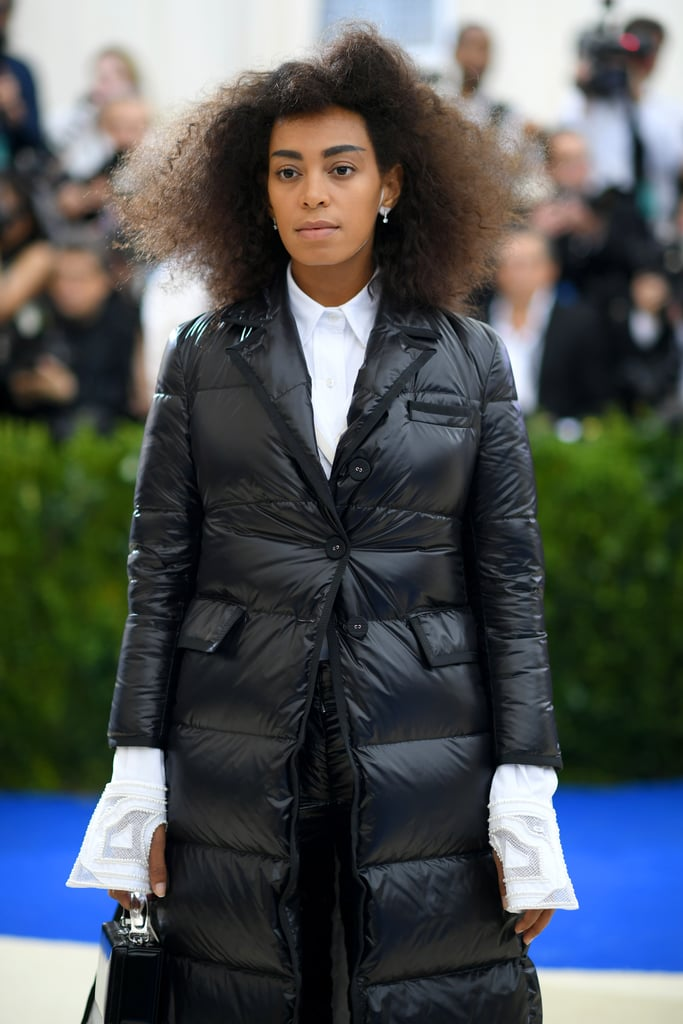 Though some stars opted for sexy skin-tight dresses at this year's Met Gala, Solange Knowles went a more comfortable and covered-up route, and we're so into it. The singer practically glided her way down the red carpet sporting a Winter-ready ensemble by Thom Browne.  Her shiny black puffer coat (which included an unexpected train) paired perfectly with equally puffy pants and a white button-down shirt. But the chilly weather vibes didn't stop there, as the star also rocked a pair of oxford shoes with an ice-skate-inspired heel. Although her attire may somewhat resemble a sleeping bag, she stuck to the avant-garde Met Gala theme like a pro. Ahead catch a glimpse at Solange's cozy-cool look, which reminds us of a goth off-duty ice skater — in the best way possible.