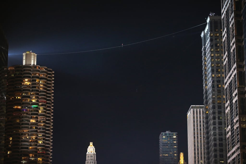 Chicago residents gathered downtown on Sunday to watch daredevil Nik Wallenda walk a tightrope between three tall buildings in the city, marking yet another of his incredible stunts. Last year, Nik made headlines when he walked a 1,400-foot tightrope across the Grand Canyon, becoming the first person to do so. This time, it was a two-part walk, and Nik started at the Marina City west tower, walking on a 19-degree incline to the Leo Burnett Building — a total of 454 feet. For the second stage of the walk, Nik was blindfolded, walking a 94-foot tightrope 543 feet above the ground between two Marina City towers. No nets or safety harnesses were involved, and both walks broke world records. Take a look at incredible pictures from the event, plus a video of Nik's impressive stunt. Source: Getty / Scott Olson
