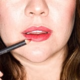 To start, apply a lip pencil in a matching shade all over lips — this will act as a base for the gloss and lipstick. I used a red shade, like Laura Mericer Lip Pencil in Warm Poppy ($24).