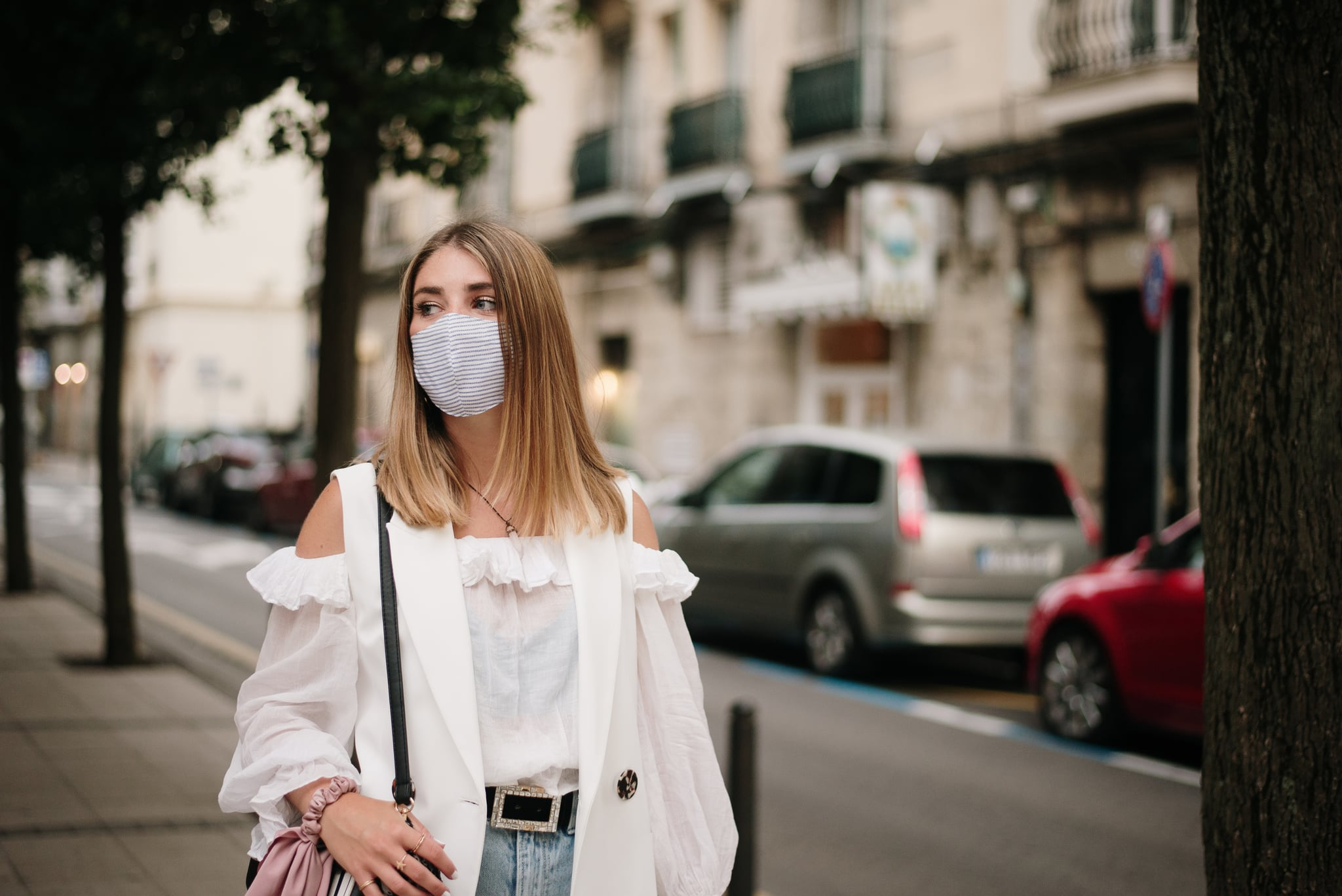 A young woman in a city street, wearing a protective face mask during the COVID-19 pandemic
