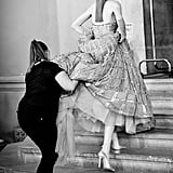 A model is helped up the steps in a voluminous Zuhair Murad gown.