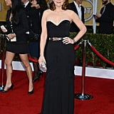Tina Fey looked effortlessly glamorous in a strapless corseted Oscar de la Renta gown. A metallic belt, matching clutch, and retro waves took her SAG Awards ensemble to new heights.