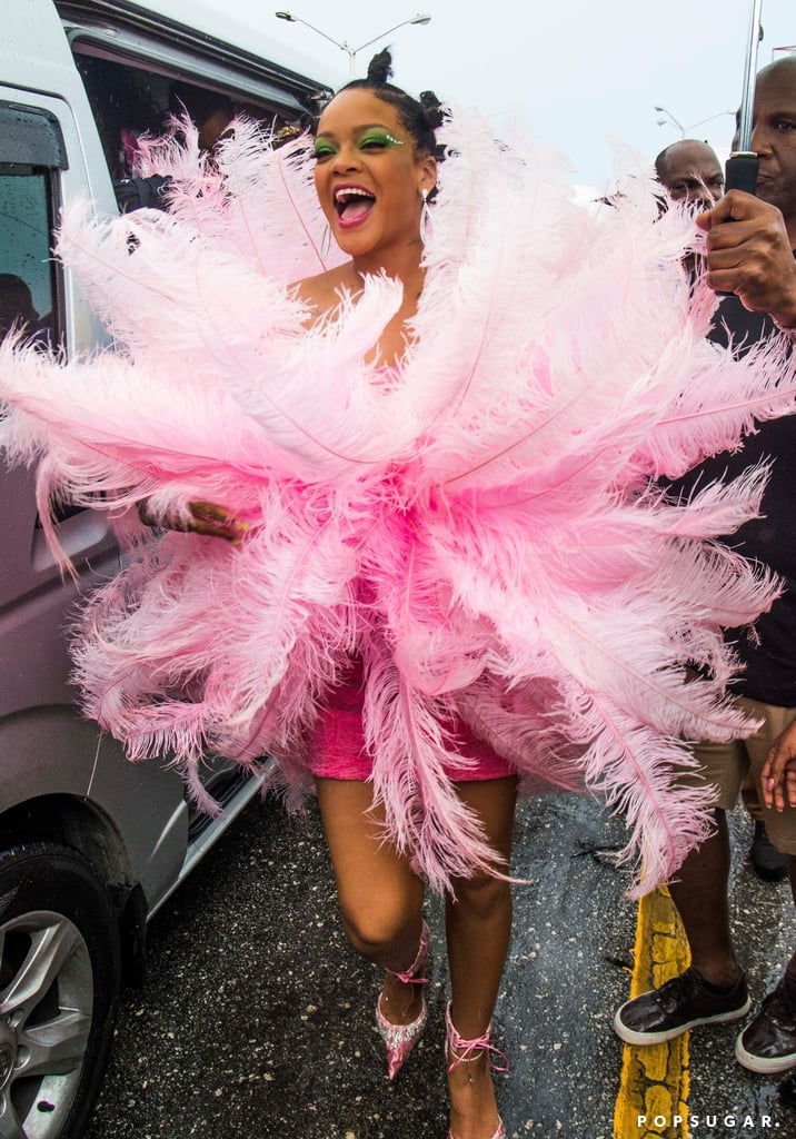 Rihanna is currently living her best life at Crop Over Carnival in her hometown, Barbados. On Monday, the 31-year-old singer was spotted at the festival in a strapless pink dress which was covered in feathers. She accessories her look with bright green eyeshadow, dangling earrings, a pair of studded sunglasses, and her hair in bantu knots. Rihanna just couldn't hide her smile as she arrived at the event, which marks the end of a successful sugar cane harvest. The singer is a longtime attendee of the festival. In 2017, she participated in the annual Kadooment parade wearing a jewel-encrusted bikini and turquoise hair. She even documented her appearance at the festival with a series of sexy photos. See her most recent trip to the Crop Over Carnival ahead.