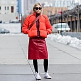 With an Orange Puffer Jacket, a Red Leather Skirt, and Black Tights