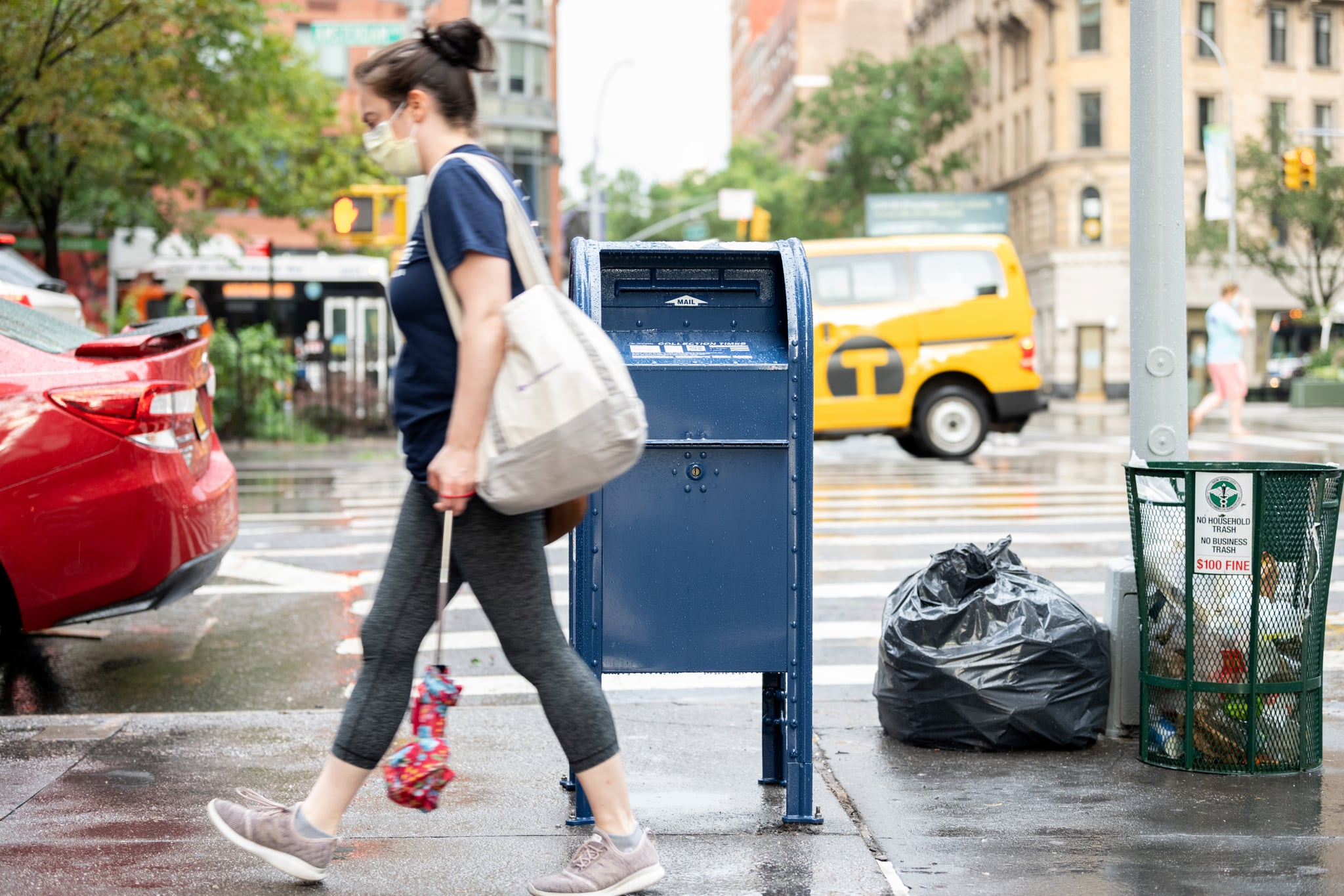 NEW YORK, NEW YORK - AUGUST 25: A woman wearing a mask walks past a USPS mailbox as the city continues Phase 4 of re-opening following restrictions imposed to slow the spread of coronavirus on August 25, 2020 in New York City. The fourth phase allows outdoor arts and entertainment, sporting events without fans and media production. (Photo by Alexi Rosenfeld/Getty Images)