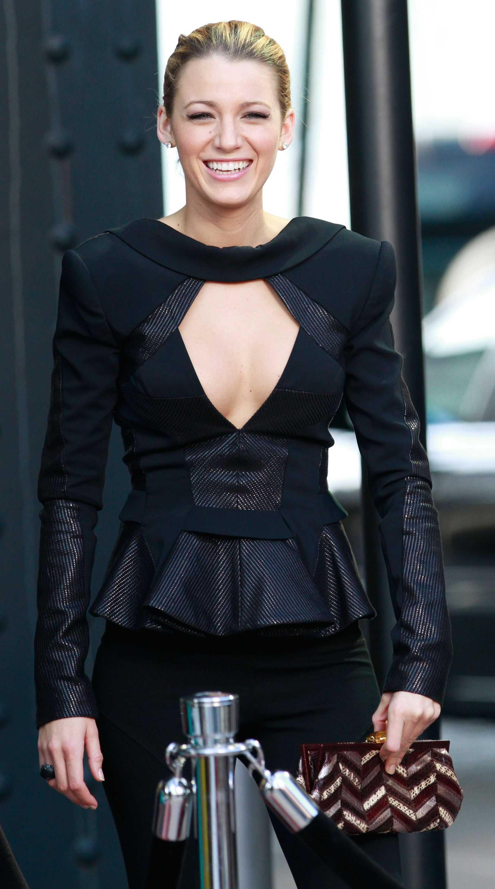 Blake Lively wore a dramatic black peplum top and bright smile, while shooting on location in NYC in August 2010.