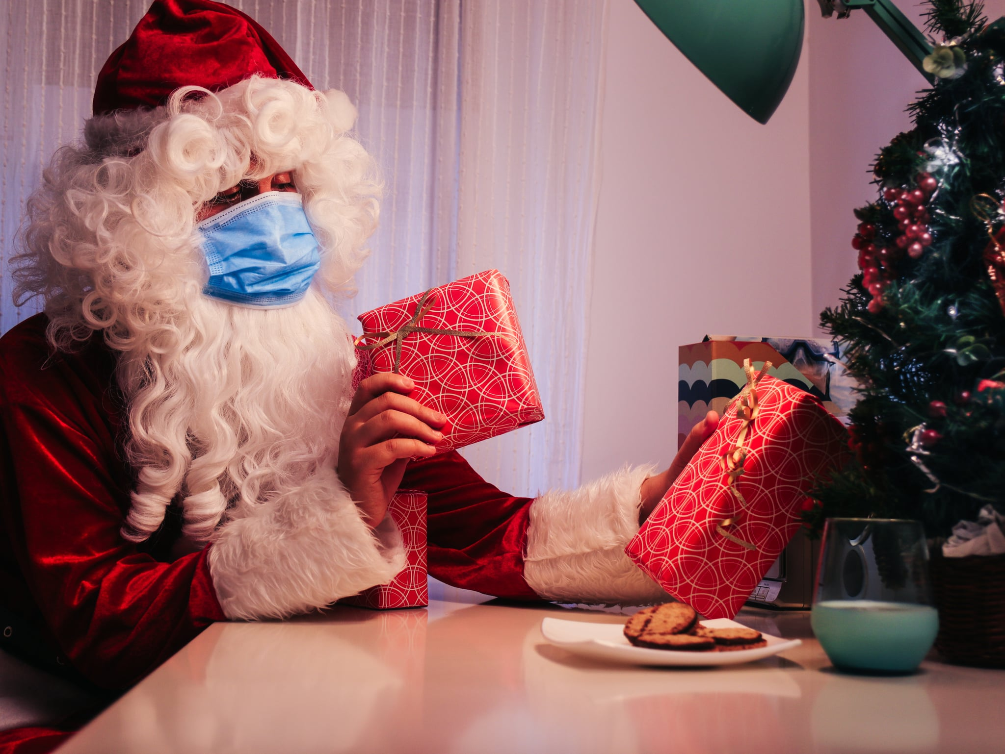 santa claus inside a house with a blue face mask, a glass of milk and cookies putting gifts on christmas tree