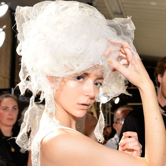 """""""Nothing's too over the top,"""" Jon Pulitano (Redken) said of the three different hairstyles he created for Akira. The first style — for the bridal look — was """"ethereal, fluffy and twisted,"""" and he used Redken Rootful 06 to bring it to life. The second — for the colour section — was a high ponytail """"looped around and pinned down into a shell-like shape. It's almost a reverse chignon."""" Fashion Works 12 and Forceful 23 played a key role in creating that style. And lastly, for the print section, Pulitano created a low ponytail with a centre part, looped around on itself. They were teamed with three different makeup looks, too. Kate Squires (Napoleon Perdis) said the first was all about sheer skin and a sparkly eye that is """"not too overpowering"""" and created using the brand's Disco Glitter. The second makeup look focused on a matte red lip and the third was about flushed skin and a lip stain """"as though she's been sucking on berries."""" It was finished with a """"poolside blue eye"""" that was slightly extended. Take a look at the different beauty looks now."""