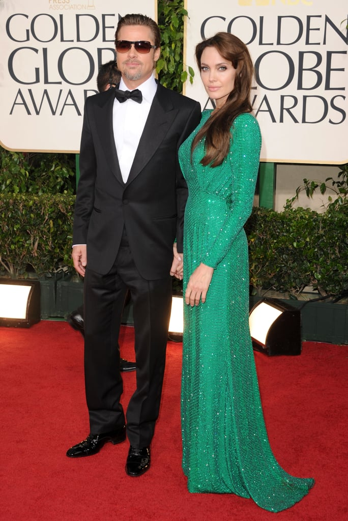 Angelina Jolie opted for a stunning green Versace gown for yesterday's Golden Globes red carpet. She had her best accessory, Brad Pitt, on her arm, and he was decked out in a dashing suit from the same designer. Brad also went with slicked back hair and kept his shades on while they posed together. What's your take on their fashion tonight? Weigh in with all of Fab and Bella's live love it or leave it polls and stay tuned for lots more from the red carpet!