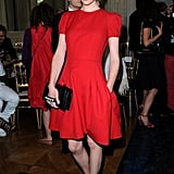 Clemence Poesy struck a pose in a cherry-red fit-and-flare dress in Valentino's front row.