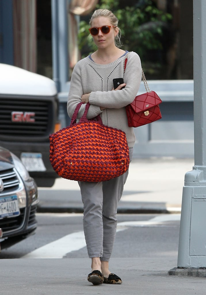 Sienna Miller looked laid back in gray cropped jeans, a knit sweater, round sunglasses, a large crochet bag, another smaller red Roger Vivier purse, and her trusty leopard loafers in NYC.