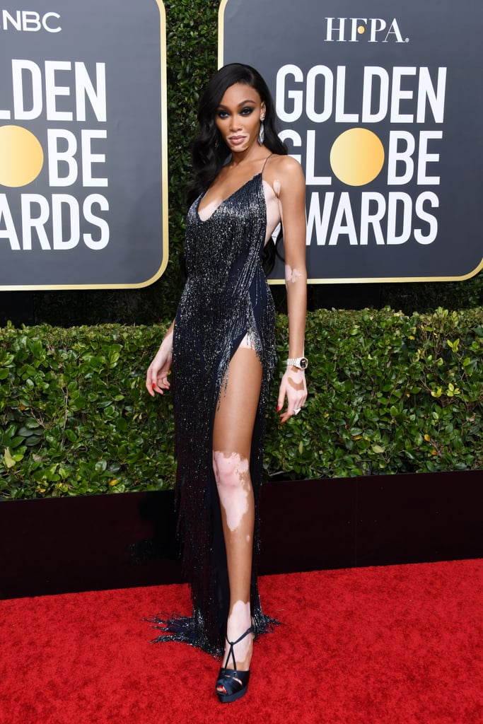 Winnie Harlow took a trip back in time to the 1920s and stunned us all with her gorgeous dress on the red carpet of the 77th annual Golden Globes — it was practically dripping with glitter and Old Hollywood charm! From the plunging neckline to the extralow back and superhigh leg slit, the beautiful gown was the epitome of a sexy statement piece.  The look, designed by LaQuan Smith, featured flapper-inspired fringe all around and made Winnie look like a classic Hollywood starlet. Winnie paired the supersexy dress with platform heels, geometric earring, and navy eyeliner that brought out the true color of the gown. Take a closer look at Winnie's dress from all angles ahead.      Related:                                                                                                           Just Some Photos of Saoirse Ronan Literally Dazzling on the Golden Globes Red Carpet