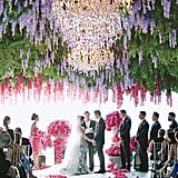 A dramatic, oversized floral display transforms a plain ceremony tent into an enchanted garden.