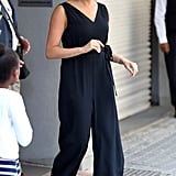Meghan, Duchess of Sussex Wears An Everlane Jumpsuit with Manolo Blahnik Pumps, and Gold Earrings