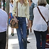 Claudia Schiffer was the picture of Spring in a soft yellow blouse and high-waist wide-leg denim.