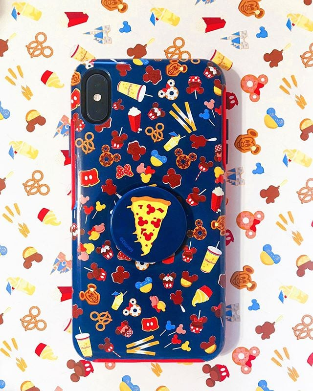 Disney has finally found a way to let me take my favourite Disney snacks with me wherever I go — in the form of a phone case. When it comes to Disney treats, we're no strangers to the theme park's Watermelon Rum Dole Whip, Lion King Bugs and Grub Waffle Cones, and Boozy Violet Slushies. And what they all have in common is they absolutely deserve to be photographed.  Now you and your Disney crew can journey through the parks with matching phone cases worthy of your most glamorous food-filled Instagram snaps. The Disney Parks OtterBox + Pop Symmetry Phone Case ($60) is available for iPhone X and iPhone Xs at Disneyland and Walt Disney World, and it's covered in pictures of Mickey Mouse-shaped ice cream, pretzels, macarons, candy apples, doughnuts, and more. Just typing this is making my mouth water. To top it all off, each phone case has a pizza pop socket — ya know, in case you want to take the perfect selfie with any Pizza Planet merch or Toy Story 4 snacks. Take a closer look at the delicious-looking phone case ahead.