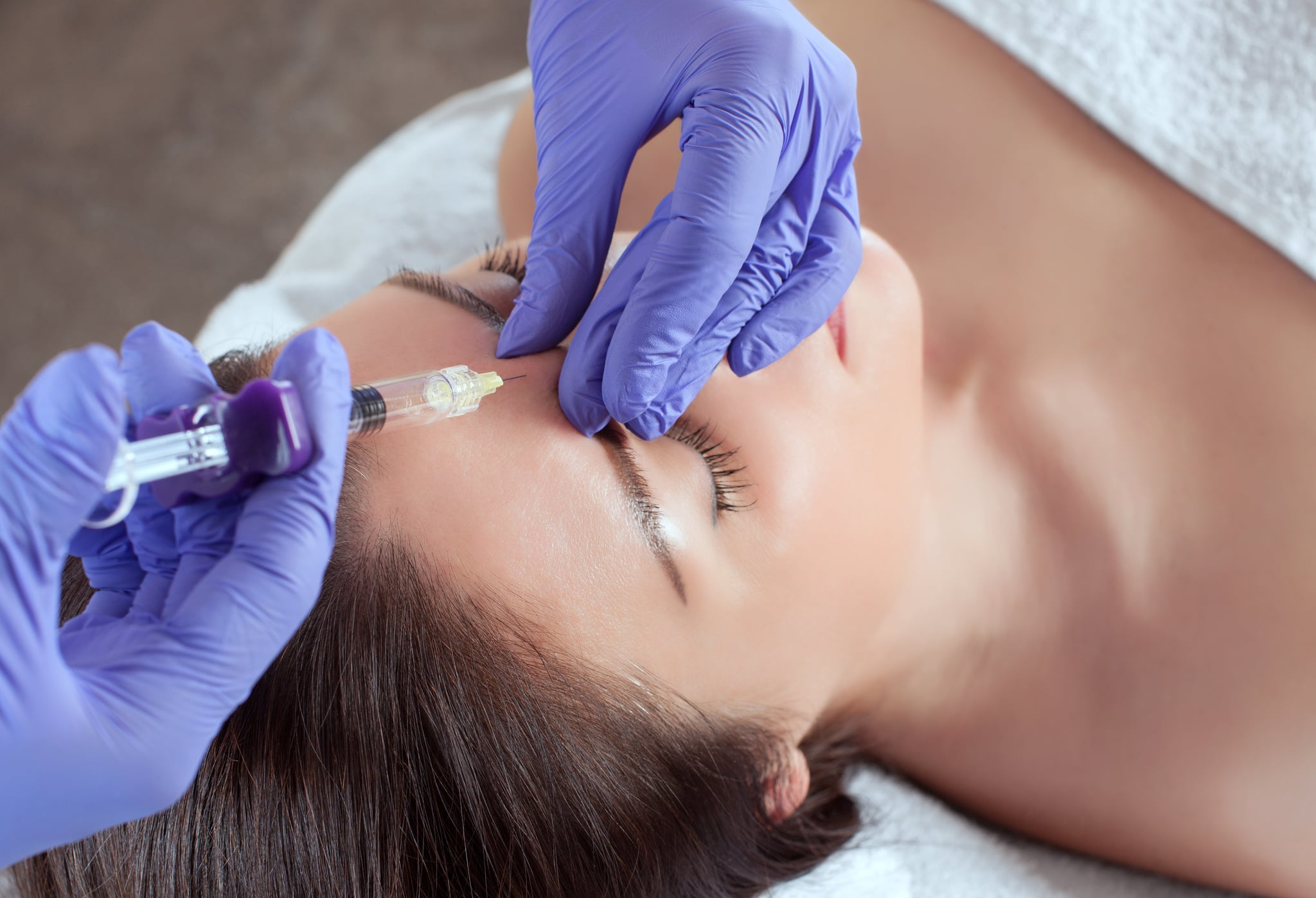 There are a woman and a cosmetologist, the woman is lying and the doctor is making the facial injections procedure for tightening and smoothing wrinkles in a beauty salon.Cosmetology skin care.