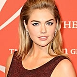Kate Upton continues to embrace the blond bombshell style with her winged eyeliner and beauty mark, but her slicked-back hairstyle was quite modern.