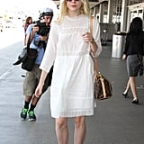 A loose white dress and pink booties really made Elle Fanning's airport outfit stand out in the crowd.
