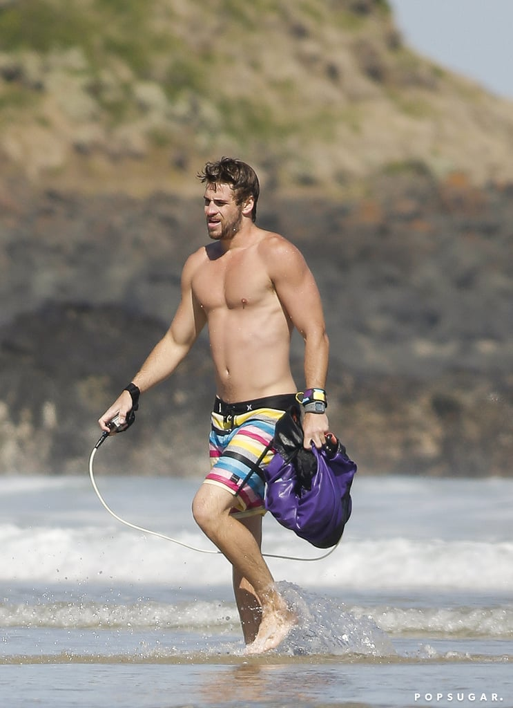 Liam Hemsworth hit the beach shirtless in his native Australia yesterday. He went body surfing with friends in the ocean and later covered up for a drink in the sand. While Liam is in his home country, his fiancée, Miley Cyrus, is back in LA. She's been spotted out multiple times without her diamond engagement ring, causing speculation that she and Liam are going through a rough patch. Last week, Miley denied rumors that they had called off their engagement on Twitter and switched focus to her latest project — she's working on new music and will release a fourth album later this year. Liam, meanwhile, is relaxing in the sun as hype gets going for the second installment of the Hunger Games series. We got a look at Gale's official Capitol portrait last week following the release of artwork featuring the rest of his Catching Fire costars.  Source: Media-Mode