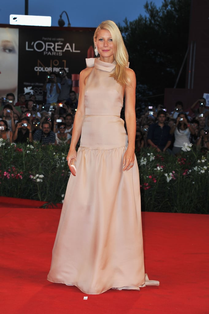 Gwyneth Paltrow looked stunning in a backless Prada gown and Bulgari earrings on the red carpet at the Venice Film Festival today. She was on hand for the premiere of Contagion after promoting the movie in an orange dress, also by Prada, at a photo call this morning. Gwyneth had costars Matt Damon, Laurence Fishburne, and Jennifer Ehle by her side for the event before the whole cast got glamorous for this evening's red carpet. Gwyneth stuck close to Matt and his wife, Luciana, on her way into the screening and showed off her goofy side by giving Matt bunny ears for the cameras.