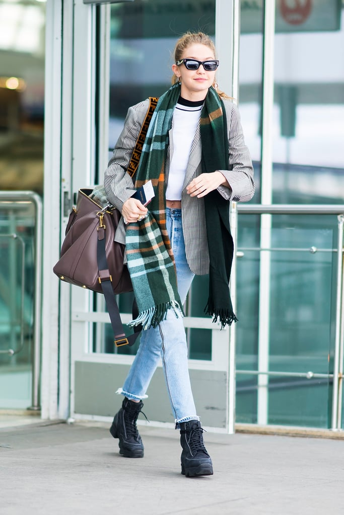Gigi touched down in NYC from Paris Fashion week in a blazer, crop top, and jeans combination. She carried her Fendi duffel bag and wore a plaid scarf and Pared x Bec and Bridge cat-eye sunglasses.