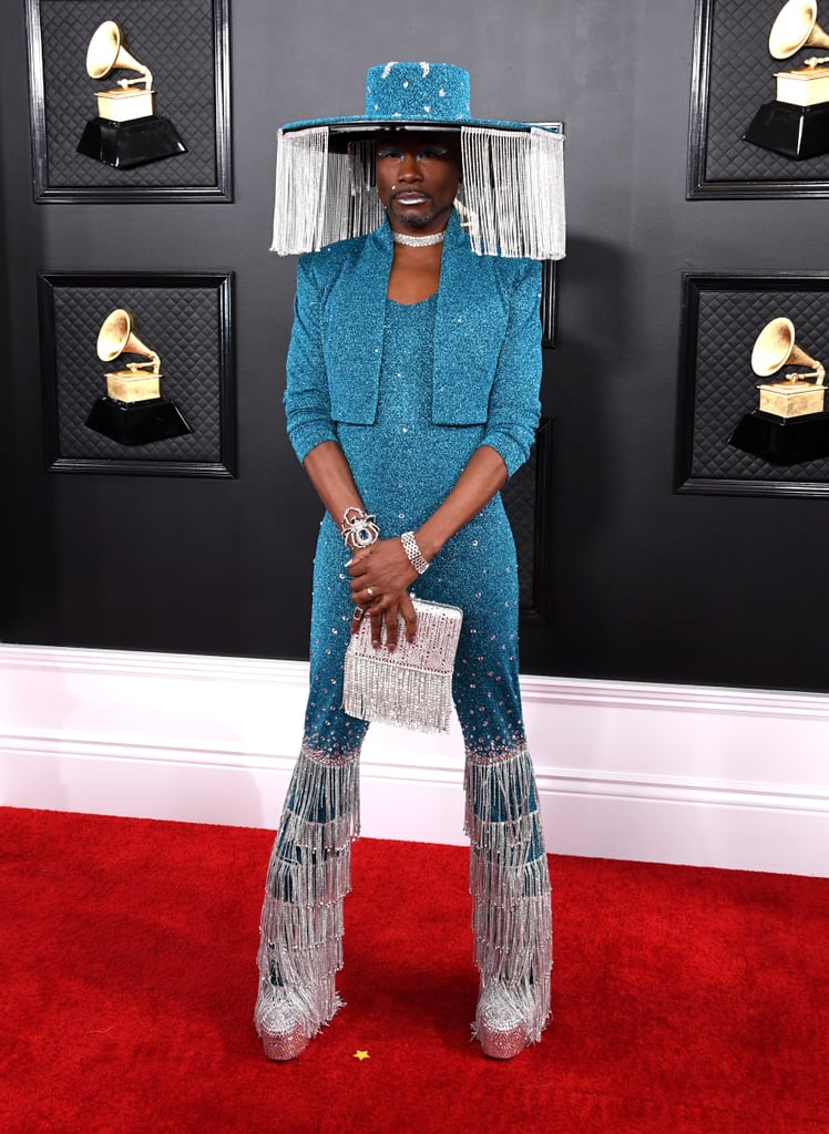 Billy Porter knows how to bring the glitz and glam to any occasion, and the Pose star truly channelled his inner Evangelista as he walked the 62nd annual Grammys red carpet on Sunday in an aqua Baja East jumpsuit with rhinestone bell-bottoms and a matching wide-brim hat that holds a very glamorous secret. The fringe-covered hat — designed by Sarah Sokol Millinery — was inspired by Billie Eilish's beekeeper-esque Burberry chain mask at the American Music Awards, according to his stylist Sam Ratelle, and features a curtain of jewels that can be opened and closed with the push of a button — now that is a look. Billy accessorised the outfit with a large bracelet shaped like a spider, a diamond collar necklace, a glittery fringe purse, rhinestone go-go boots, shimmering silver nails, and a thick blue cat eye bound to earn him an 11/10 at any ballroom show. See Billy's incredible Grammys look from all angles ahead.      Related:                                                                                                           Sorry, Lizzo Couldn't Carry a Tiny Bag With This Badass Furry Stole