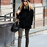 Elizabeth Olsen looked chic while walking through NYC recently. She wore skinny olive-colored jeans and a black jacket,  then accessorized her look with ankle boots, round-frame sunglasses, and gray hat.