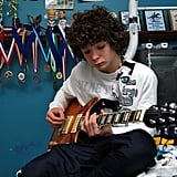 """""""He's proud that he learned how to play guitar completely on his own. He refuses to take any lessons, other than watching YouTube. Here he is, playing one of his guitars, with some of his running medals behind him."""""""