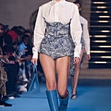 Walking in the Off-White show wearing a pair of bold blue boots.