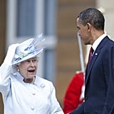 Queen Elizabeth II adjust her hat and talks to U.S. President Barack Obama in 2011